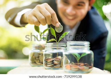 Businessman putting coin into the glass jar with young plant, demonstrating financial growth through saving plans and investment schemes Foto stock ©