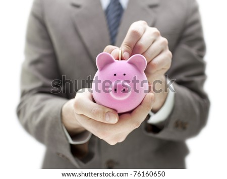 Businessman putting coin into the piggy bank - stock photo
