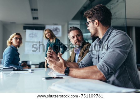 Businessman putting forward his suggestions to colleagues. Startup business team on meeting in modern bright office.