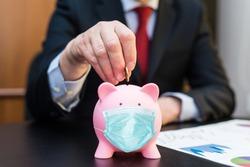 Businessman putting money in a masked piggy bank, saving during coronavirus pandemic concept