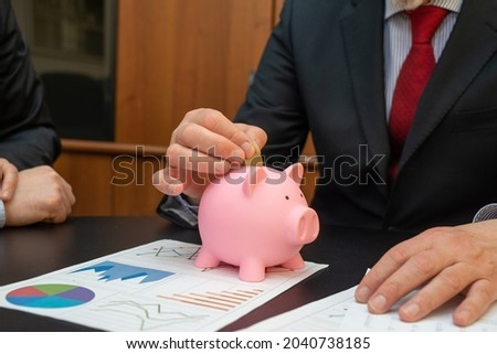Businessman putting money in the piggy bank, money save concept Photo stock ©