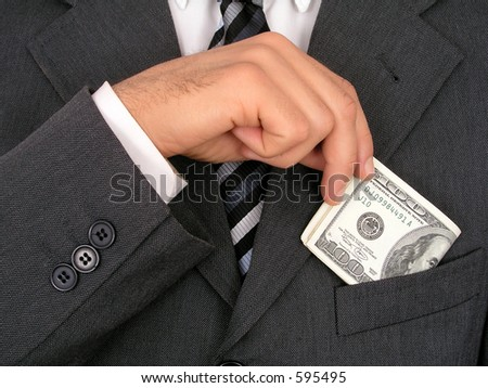 Businessman Putting Money Into Pocket - stock photo
