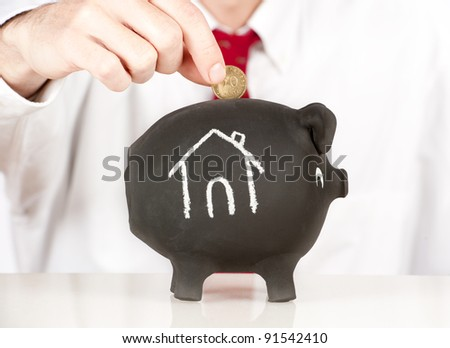 businessman putting money on a piggy bank with a house sketched