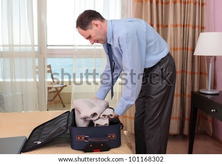 Businessman putting sweater into a suitcase - stock photo