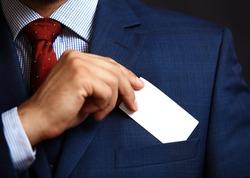 Businessman putting visit card in the pocket.