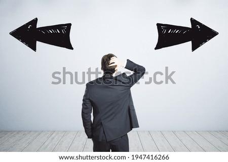 Businessman puzzled, two black arrows, right, left, path dilemma, choice concept Stock fotó ©