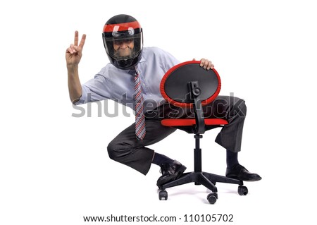 Businessman racing in a chair with helmet