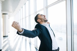 businessman raising fist and celebrating victory over office window