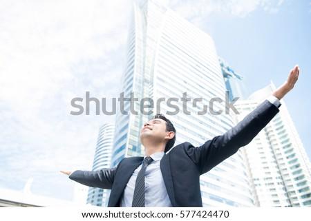 businessman raising his arms ...