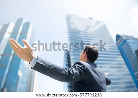 Businessman raising his arms, open palms, with face looking up to the sky - happy, success and achievement concepts #577791238
