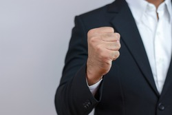 Businessman raising his fist to the front, showing determination, encouragement. Financial concepts, business growth, fighting obstacles.