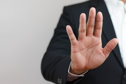 businessman raising his hand in front indicating order to stop, forbid, invalid. Corruption, illegal, anti-corruption concept.