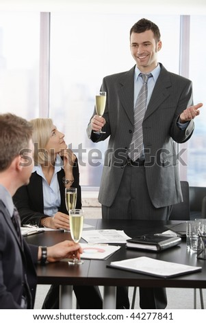 Businessman raising toast with champagne flutes, smiling.