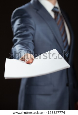 Businessman reaching out documents to you on black background