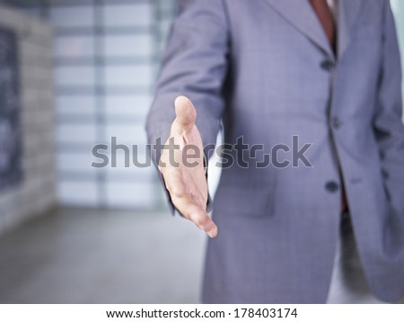businessman reaching out for handshake.