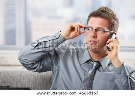 Businessman reaching up to glasses concentrating to mobile phonecall holding pen.