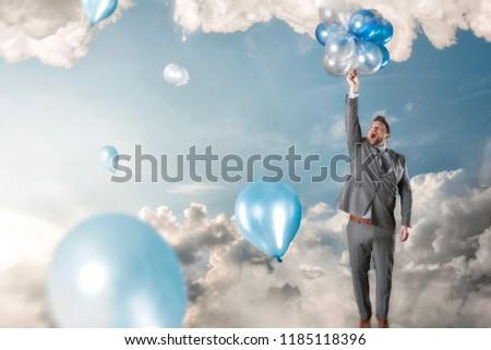Businessman reacing balloons