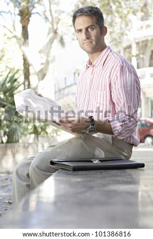 Businessman reading a financial newspaper in the city, outdoors.