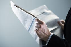 Businessman reading a newspaper, hand close up