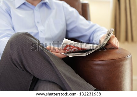 Businessman reading a newspaper whilst relaxing on a sofa - stock photo