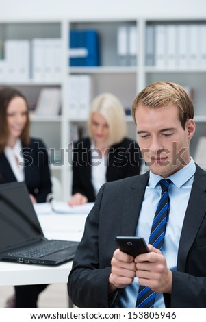 Businessman reading a text message on his mobile phone while sitting in a busy corporate office