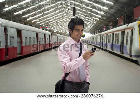 Businessman reading an sms at a train station