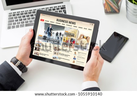 Businessman reading business news on tablet. All contents are made up.