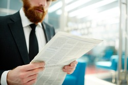 Businessman reading daily newspaper in the morning at the beginning of working day