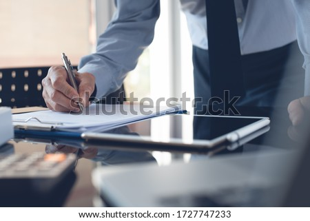 Businessman reading document before signing business contract or partnership agreement with digital tablet on desk. Corporate man, accountant working in modern office. Photo stock ©