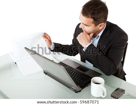 Businessman  reading documents on his desk behind laptop with cup of coffee and cellular