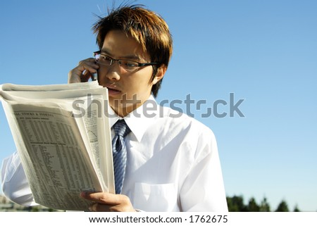 Businessman reading financial newspaper while making a phone call
