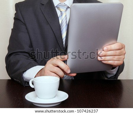Businessman reading news on tablet and drinking coffee