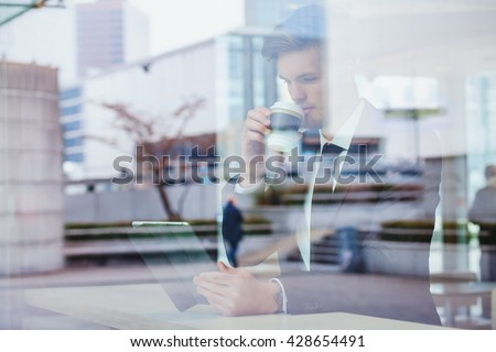 businessman reading news online and drinking coffee in airport cafe #428654491