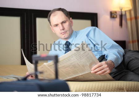 Businessman reading newspaper in a hotel room