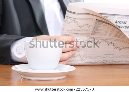 Businessman reading newspaper with tea or coffee at office