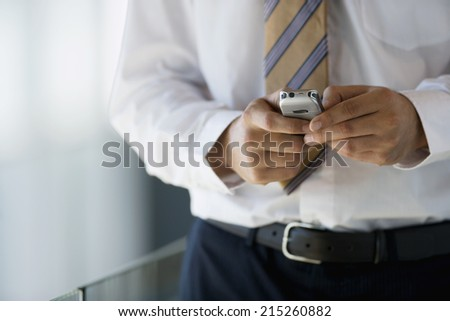 Businessman reading text message on mobile phone, close-up, mid-section