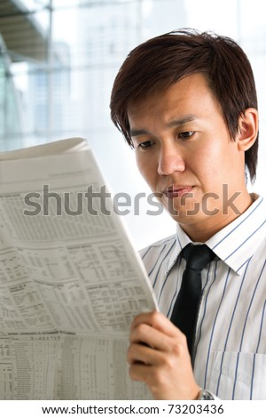 Businessman reading the business section of a newspaper.