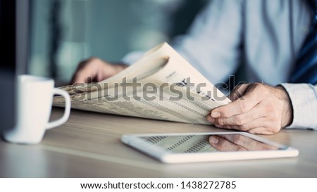 Businessman reading the newspaper on table