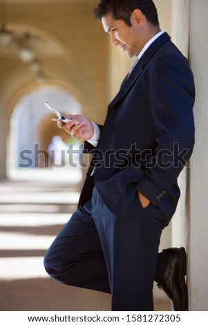 Businessman reads text message on mobile phone outdoors