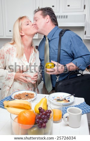 Businessman Ready for Work Kisses Wife In Kitchen.