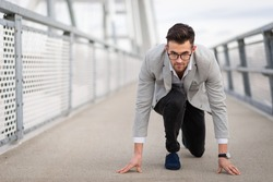 Businessman ready to run on the bridge. Focused yuppie ready to start with copy space
