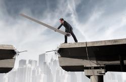 Businessman rebuilding a broken bridge