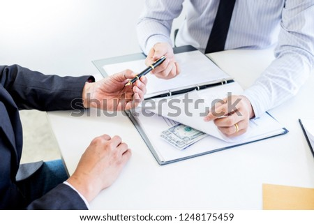 Businessman receive money in the envelope offered in file taking bribe and signing a contract - anti bribery and corruption concepts #1248175459