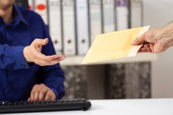 Businessman receiving a padded envelope sitting on a desk at office