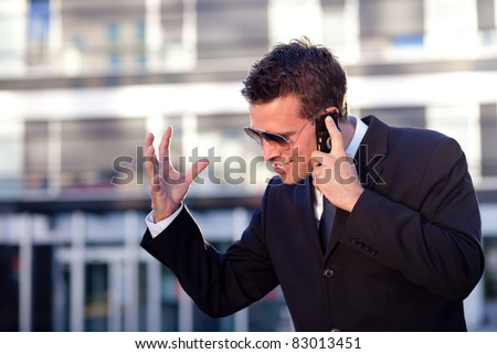 Businessman receiving bad news in front of an office building