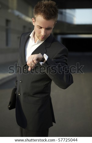 Businessman regarding time - stock photo