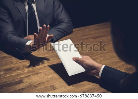 Businessman rejecting money in white envelope offered by his partner in the dark - anti bribery concept Foto stock ©