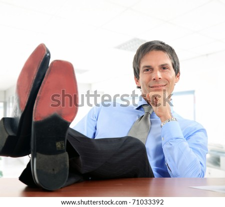 Businessman relaxing at the office with his shoes on the desk