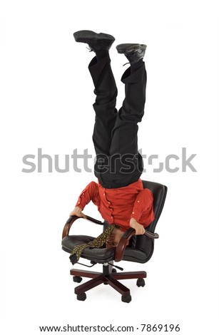 Businessman relaxing office chair standing on his head - isolated