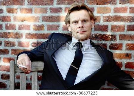 Businessman relaxing on a bench outside, smoking a cigarette, with red wall in background - stock photo